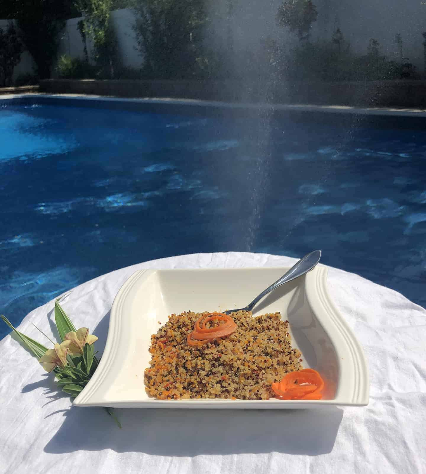 quinoa with carrot spirals in a white bowl with a spoon sitting on a white table with yellow flowers poolside