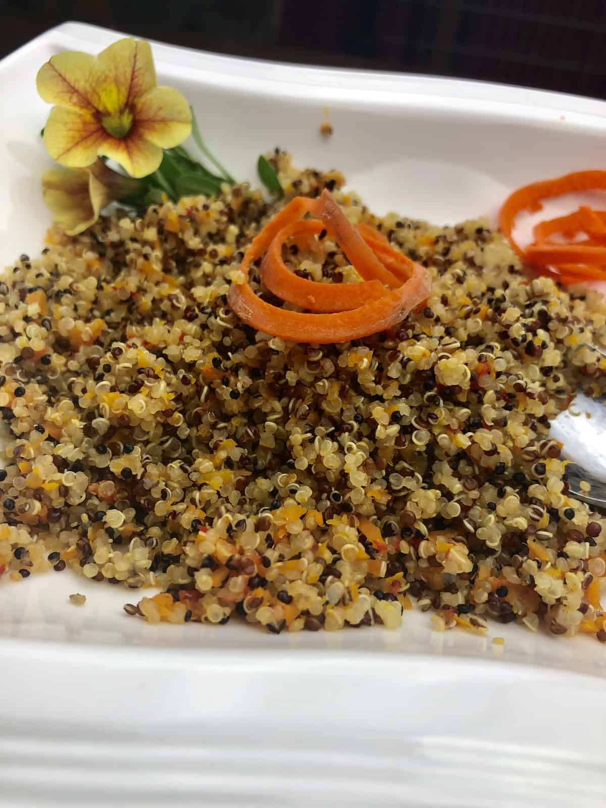 Veggie quinoa with carrot spirals in a white bowl with a yellow flower