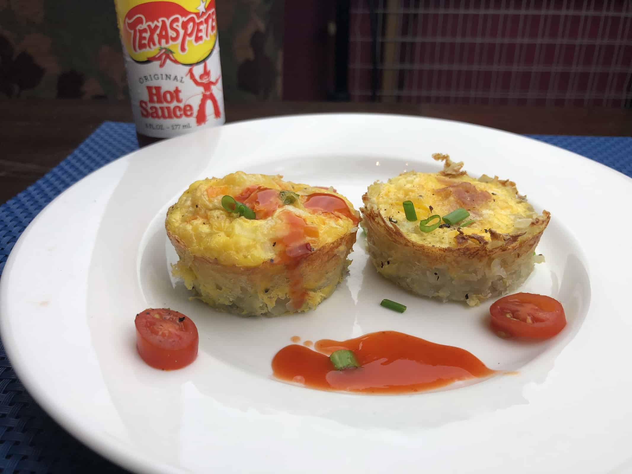 Two mini Fritattas on a white plate with hot sauce chives and tomatoes and a bottle of Texas Pete hot sauce behind the plate