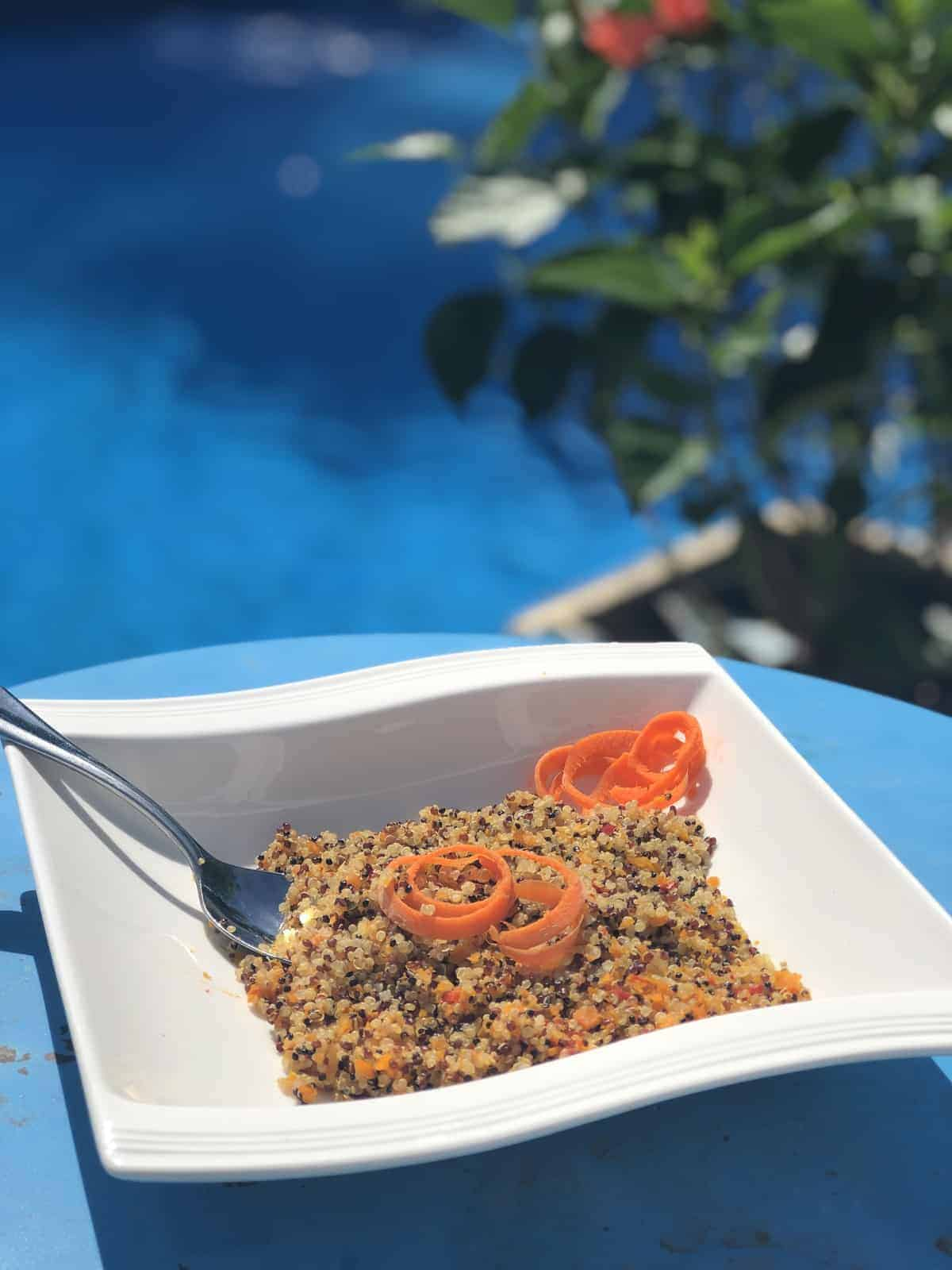 quinoa with carrot spirals in a white bowl with a spoon on a blue table by the pool