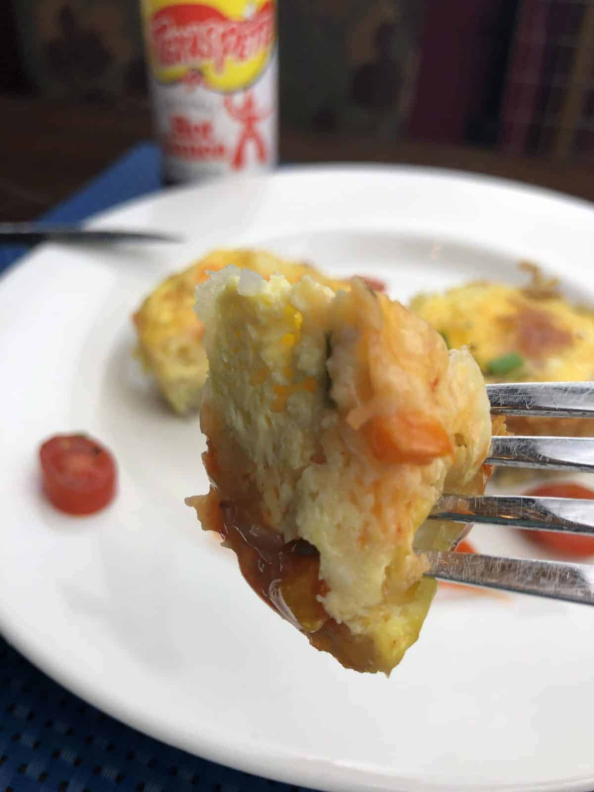 A frittata bite on a fork over a white plate with 2 mini frittatas on it with a knife
