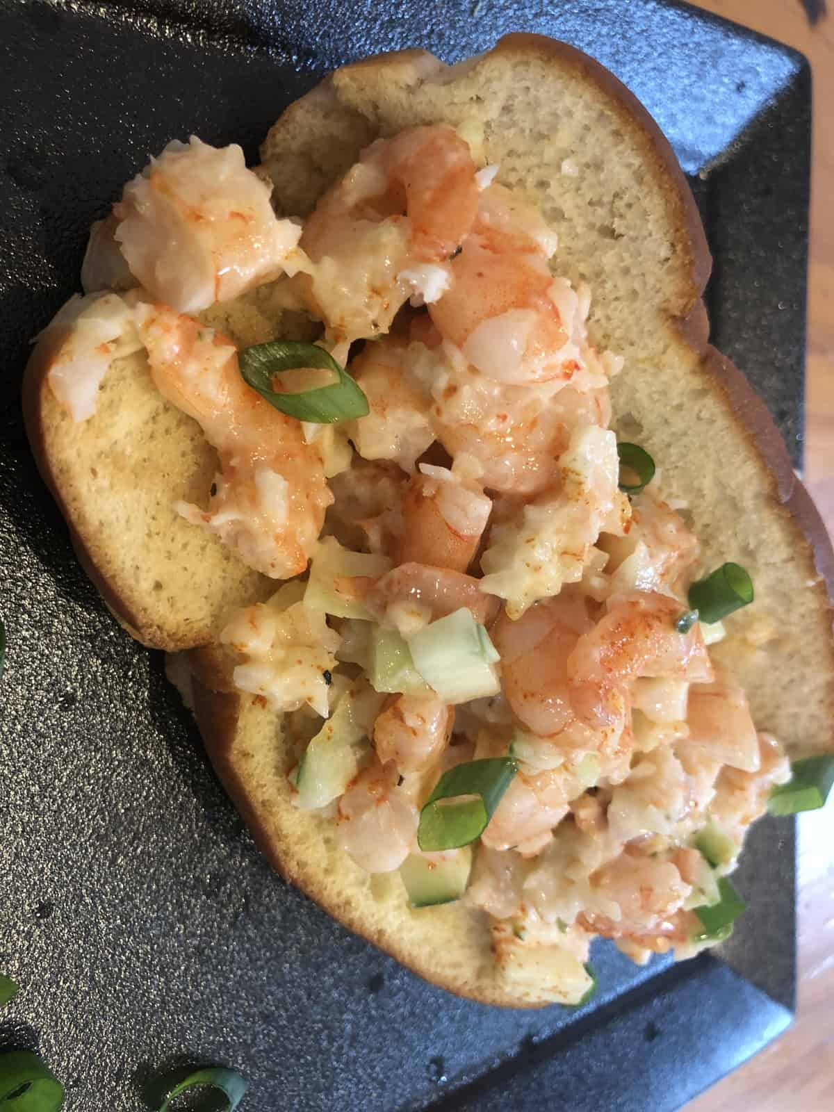 shrimp salad on a hot dog bun on a black plate
