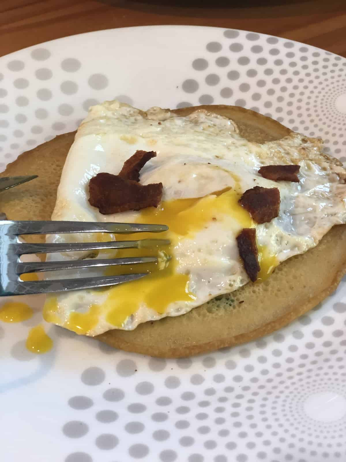 egg on a crepe with a fork on a white plate