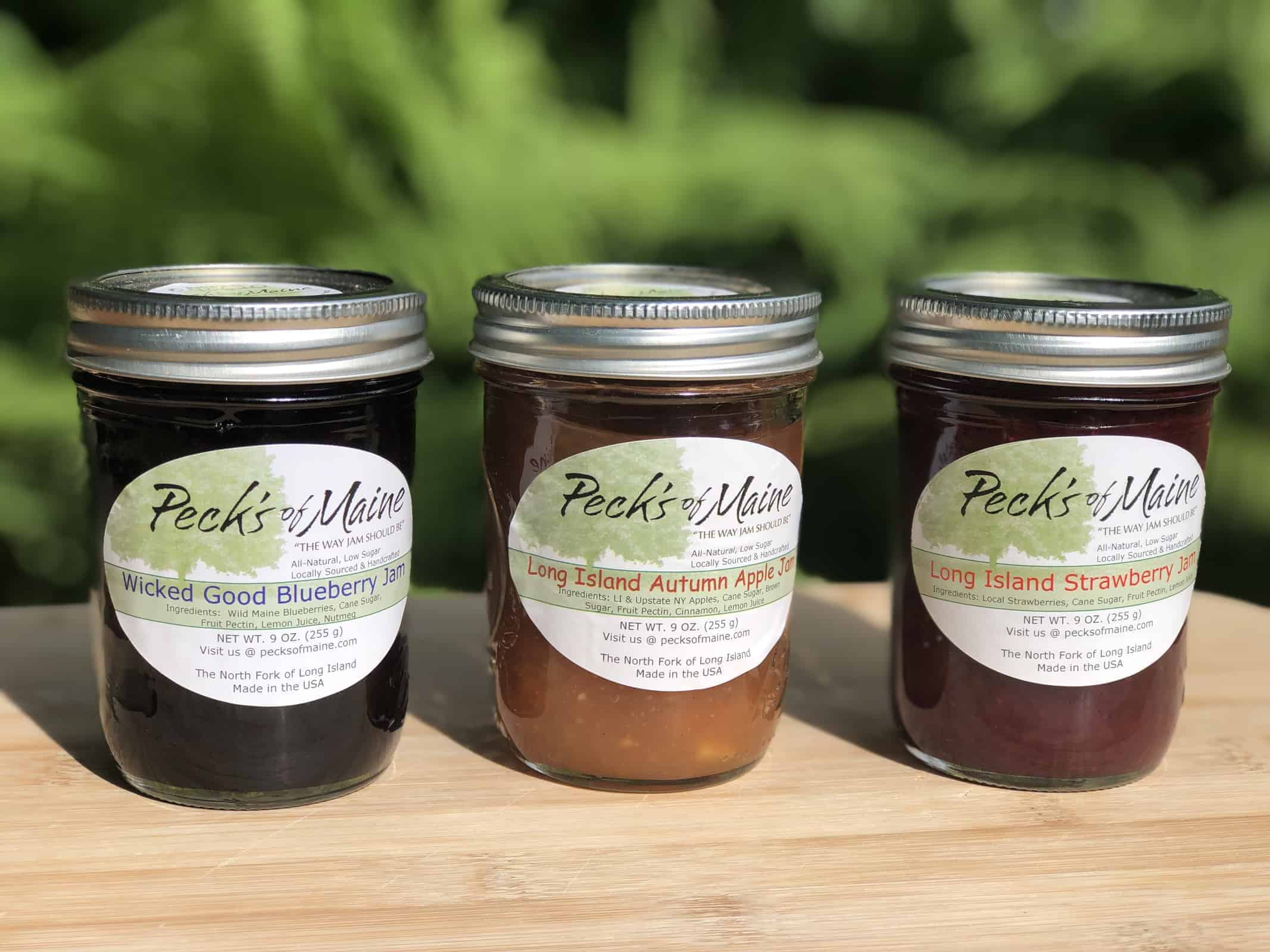 3  jars of Fresh Peck's of Maine Jams sitting on a wooden cutting board in a garden