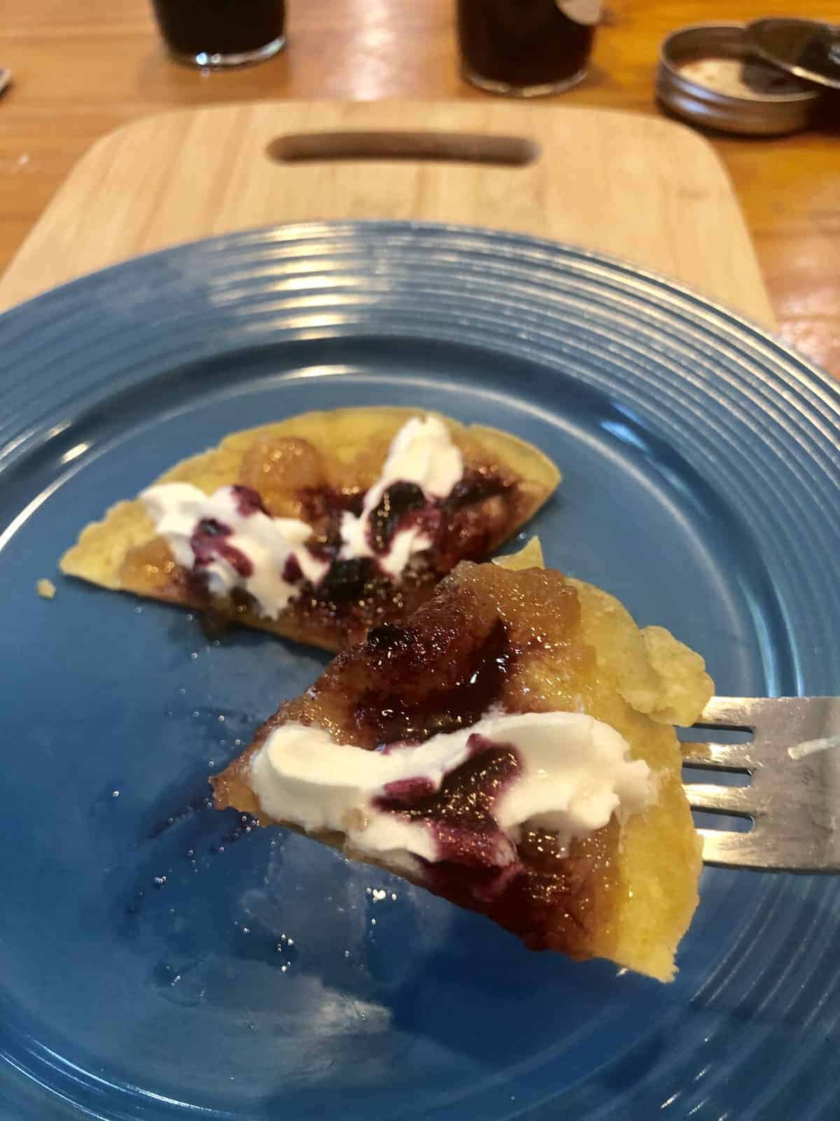 A Crepe Pizza with whipped cream and jam on a fork over a blue plate