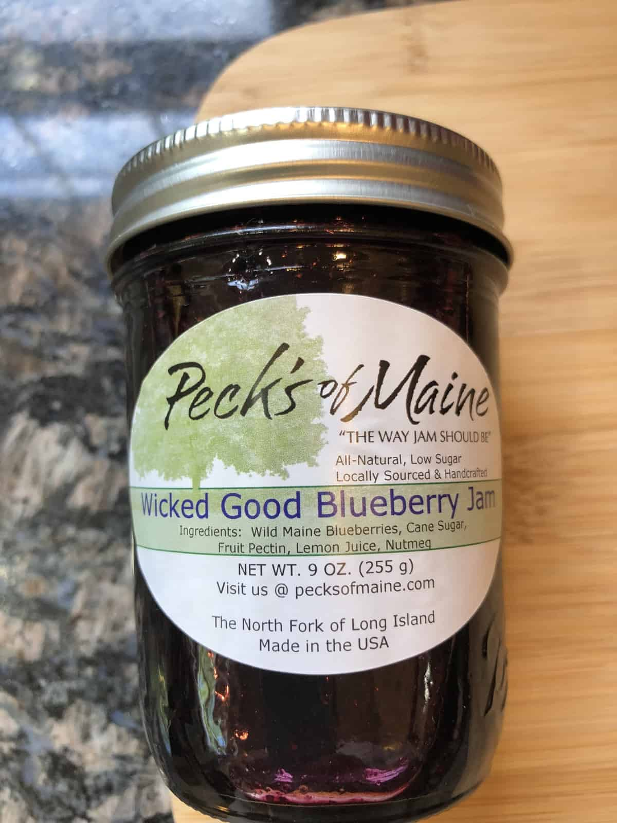 A jar of Peck's of Maine Fresh Wicked Good Blueberry Jam on a wooden cutting board