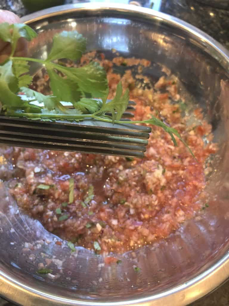 chopping fresh cilantro for homemade salsa