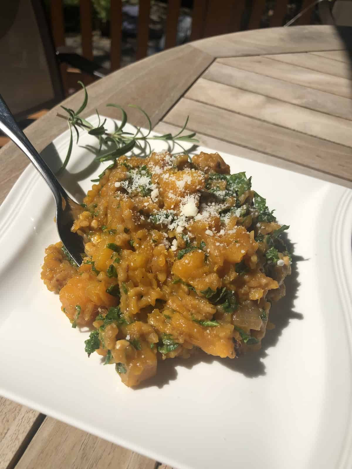 a spoonful of risotto over a plate of risotto on a wooden table