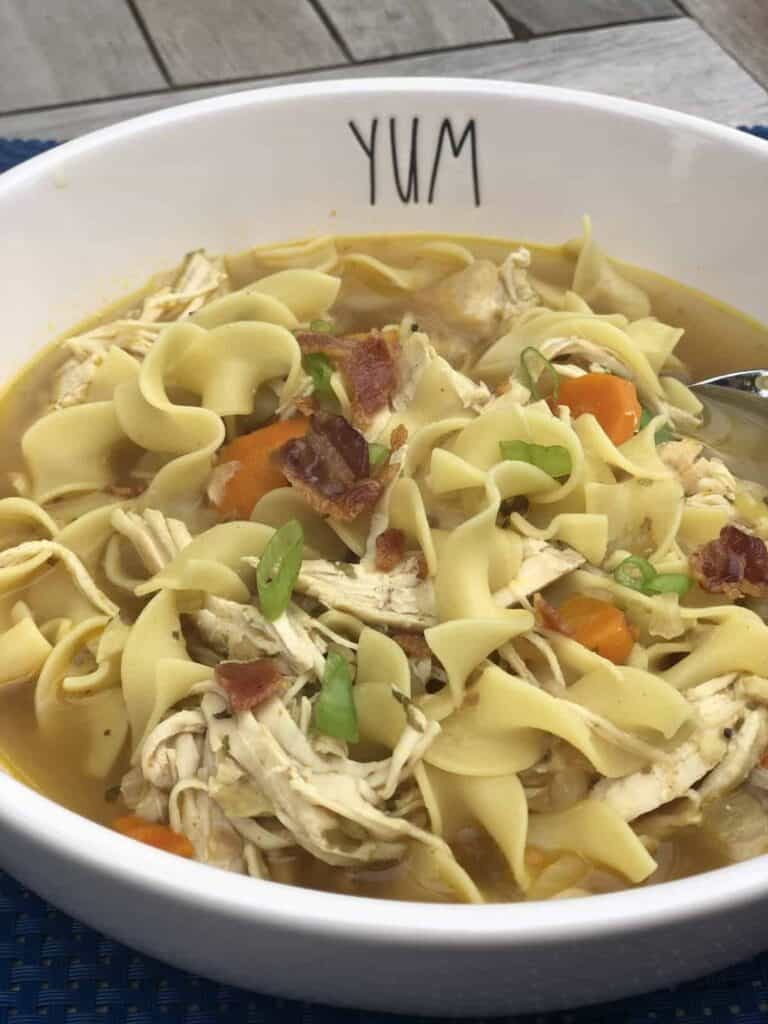 A bowl of Bacon Topped Homestyle Chicken noodle soup