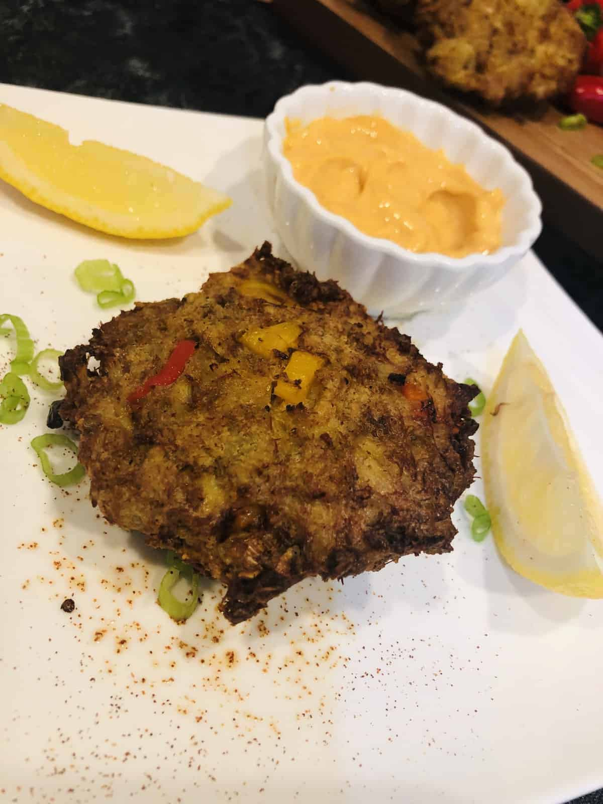 One Air Fried Crab Cake on a white plate with a lemon slice and chives and dip