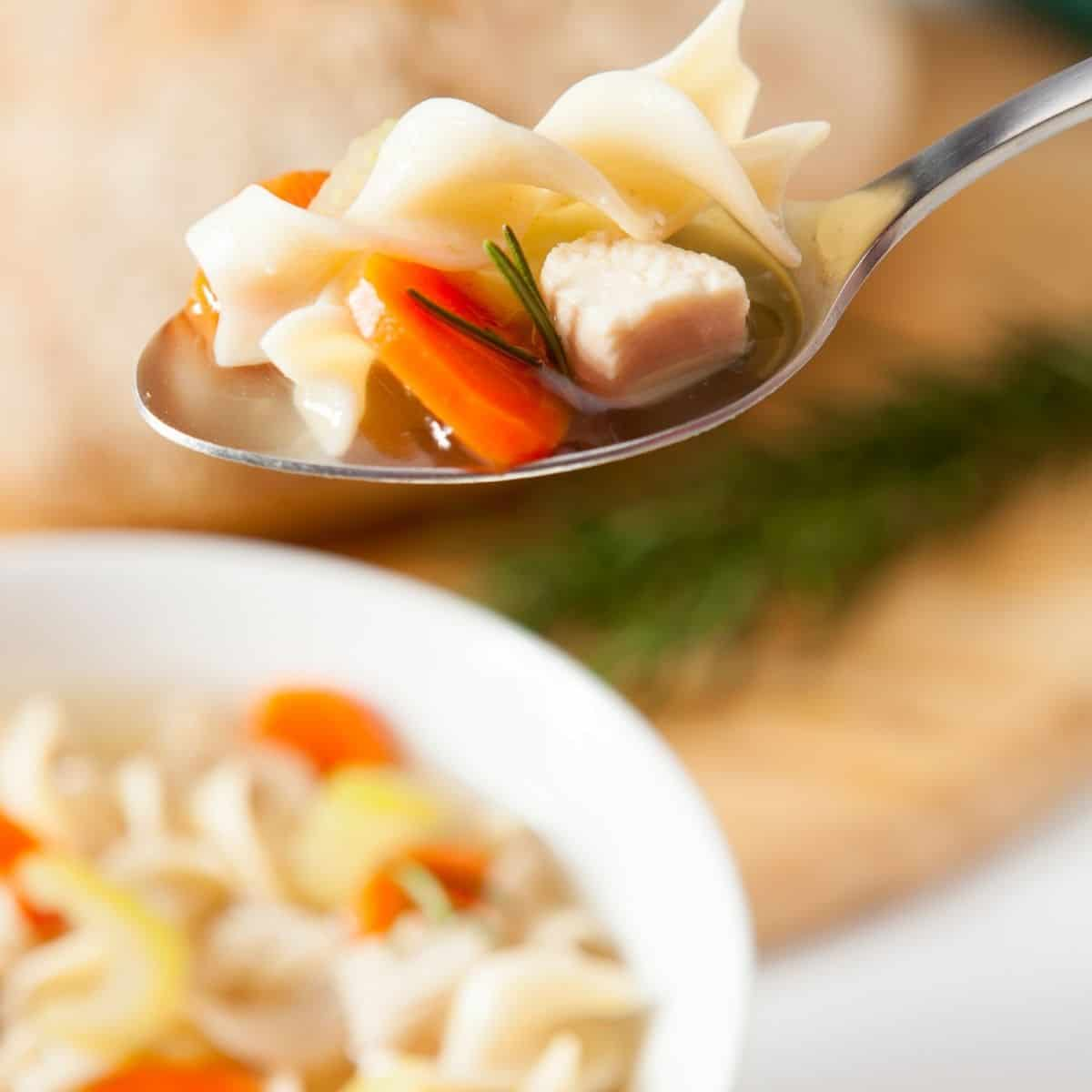 A bowl of chicken noodle soup with a spoon with a serving of noodles chicken and carrots