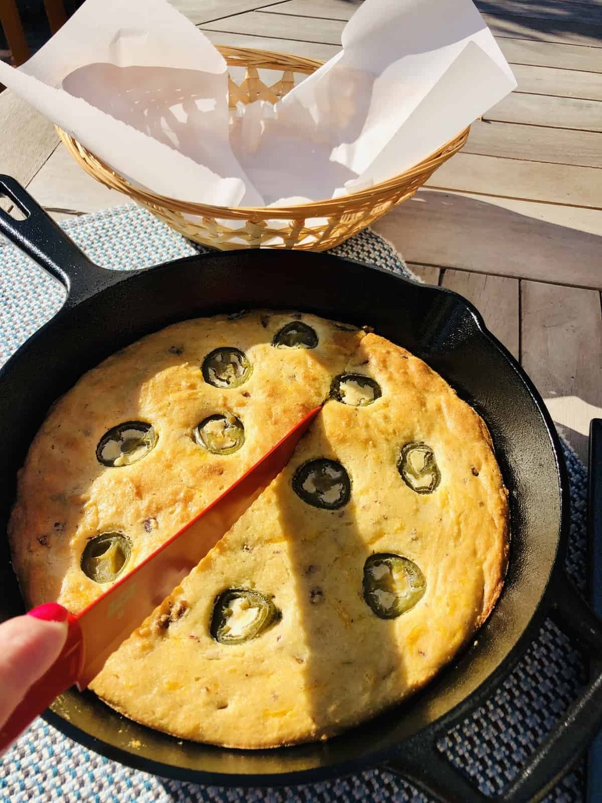 slicing keto cornbread with a red knife in a black cast iron skillet on a wooden table with a wicker basket with parchment paper