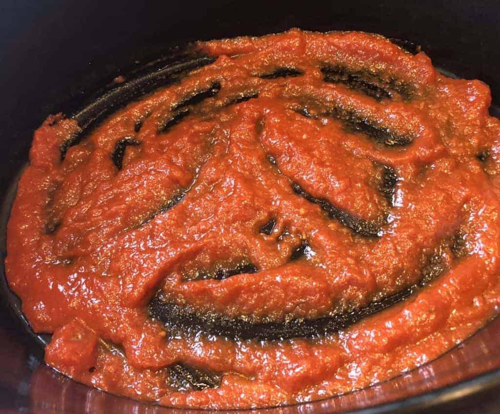 adding marinara sauce base to the crockpot