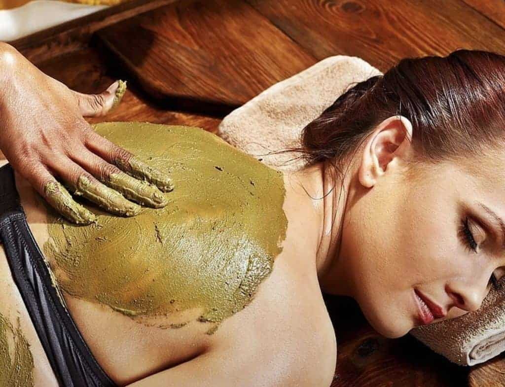 female getting body mask applied on back