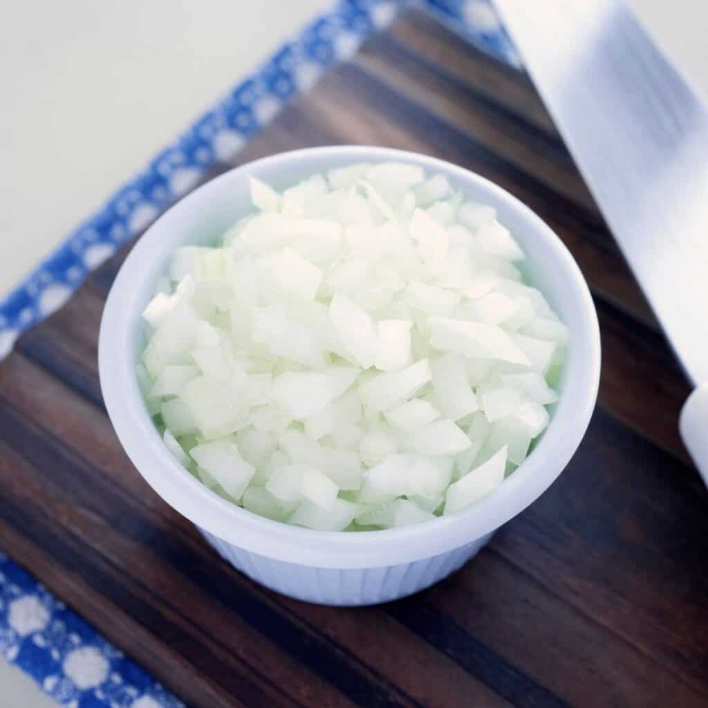 diced onions in a small white bowl