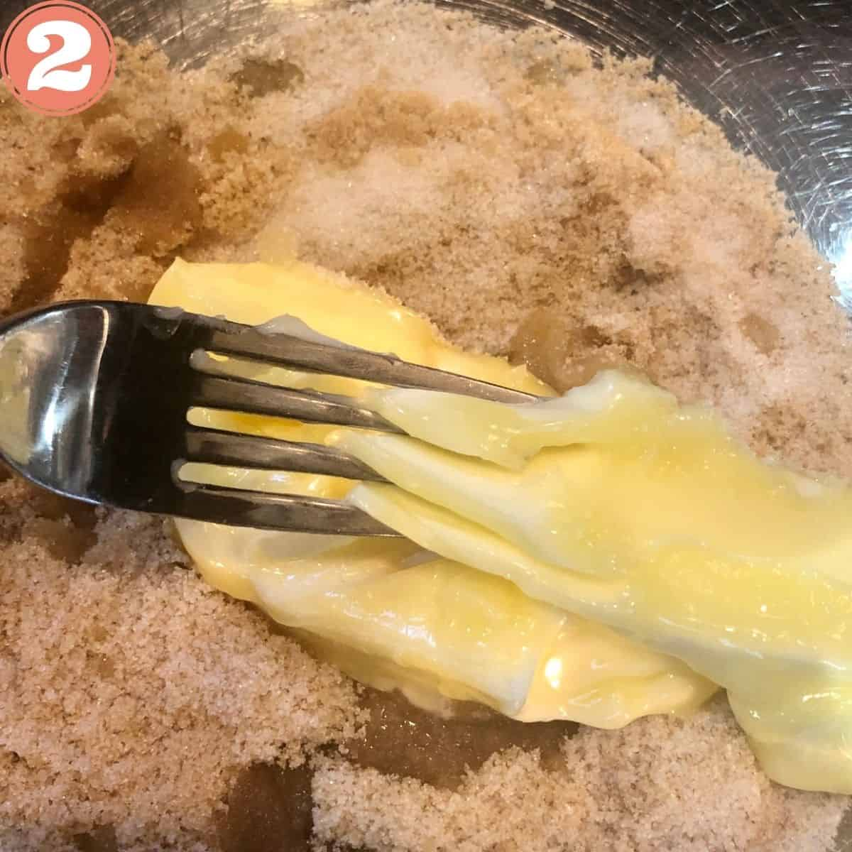 Mixing butter and brown sugar with a fork in a stainless steel mixing bowl