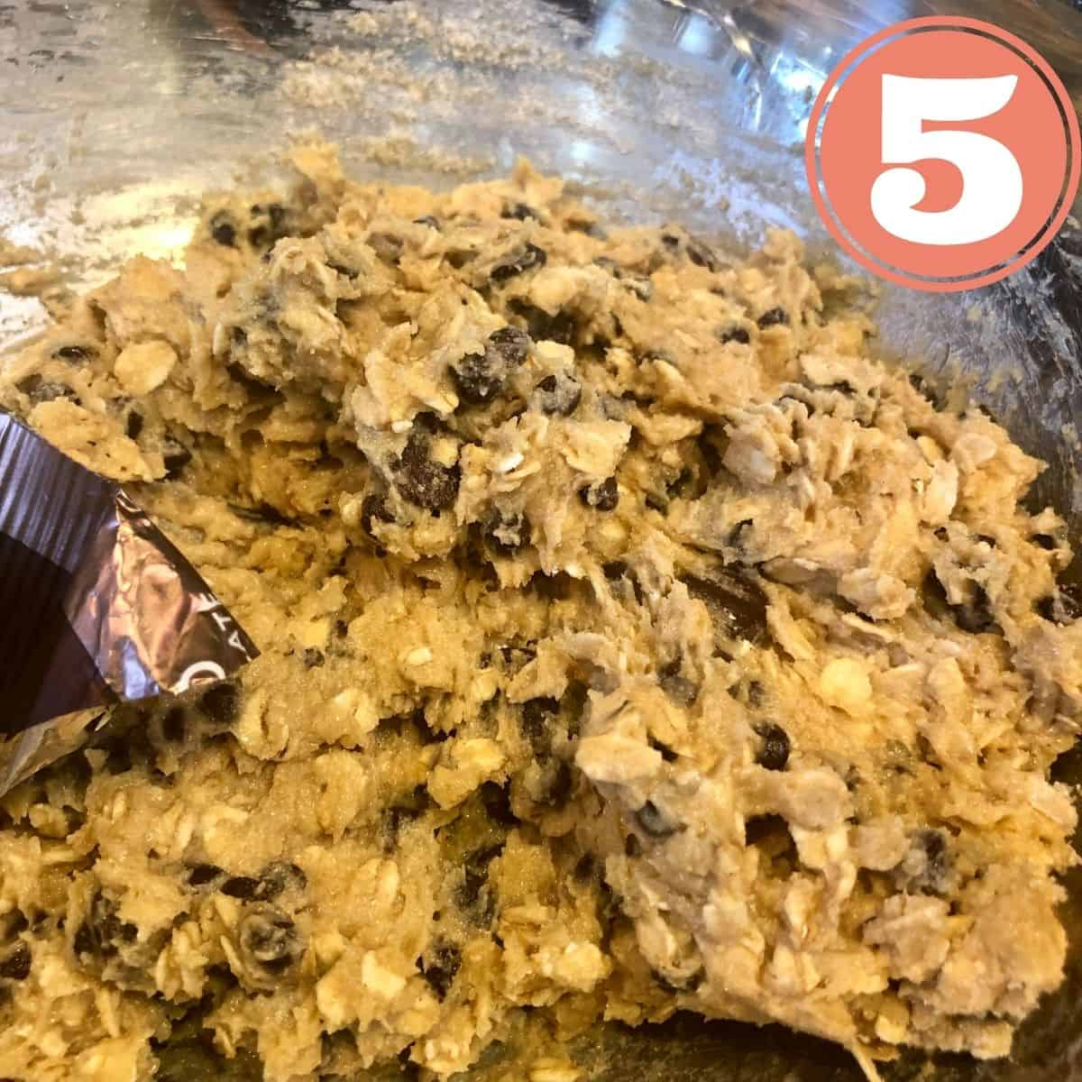 Adding chocolate chips to Oatmeal Cookie Batter in a stainless steel mixing bowl