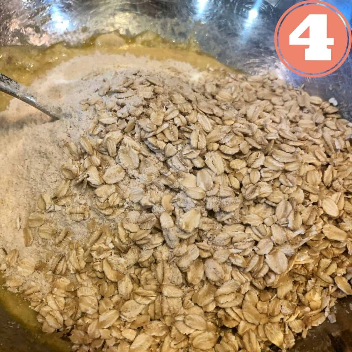Kodiak Cakes Mix and Rolled Oats in a bowl being mixed with a spoon in a stainless steel mixing bowl