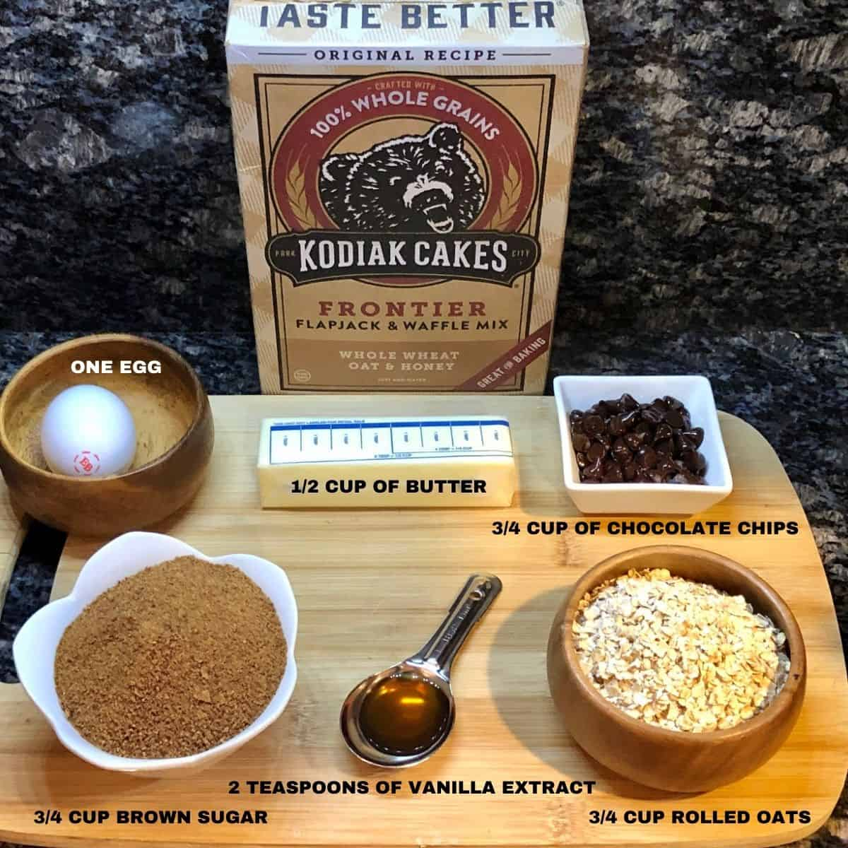 Oatmeal Cookie Ingredients Egg Butter Chocolate chips brown sugar vanilla extract and oats displayed on a cutting board