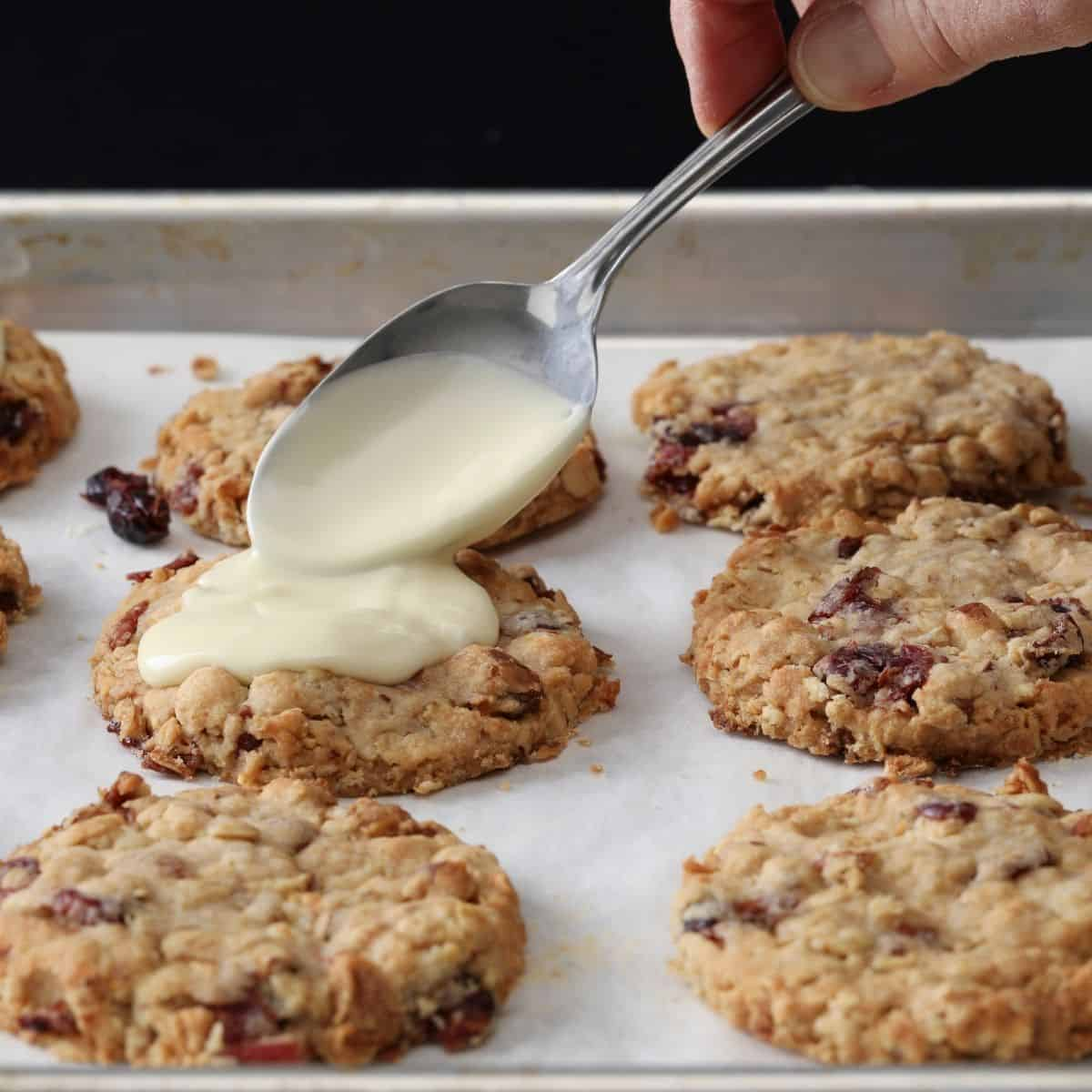 Six oatmeal cookies on a baking pan getting drizzled with vanilla icing with a spoon