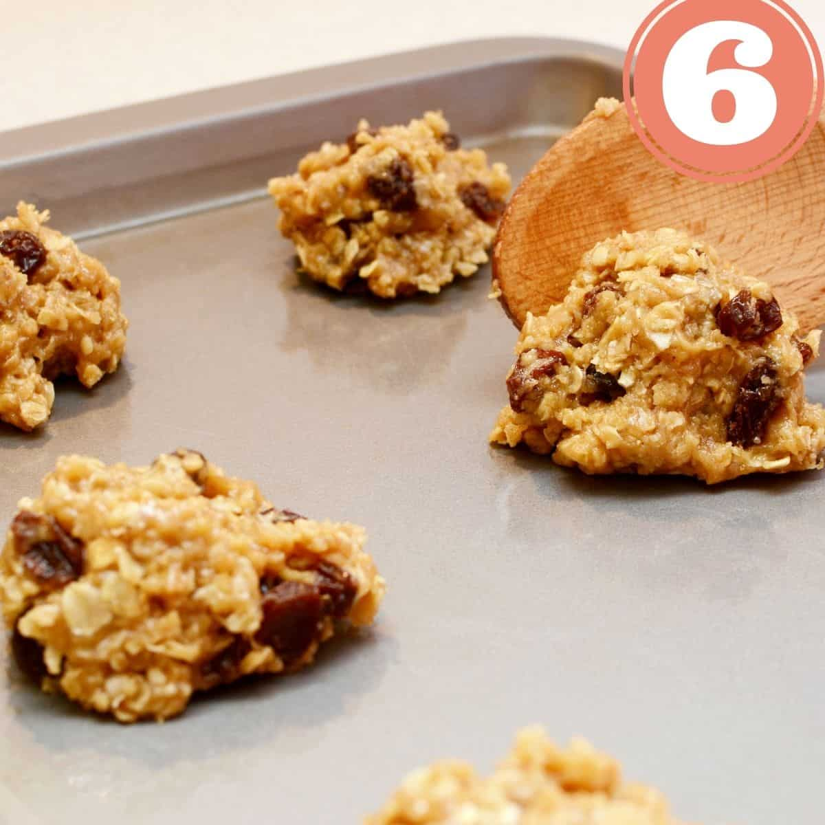 Chocolate chip oatmeal cookie batter dollops on a baking sheet with a wooden spoon