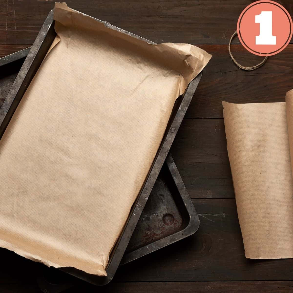 Two Baking sheet pans stacked with brown parchment paper and a roll of brown parchment paper