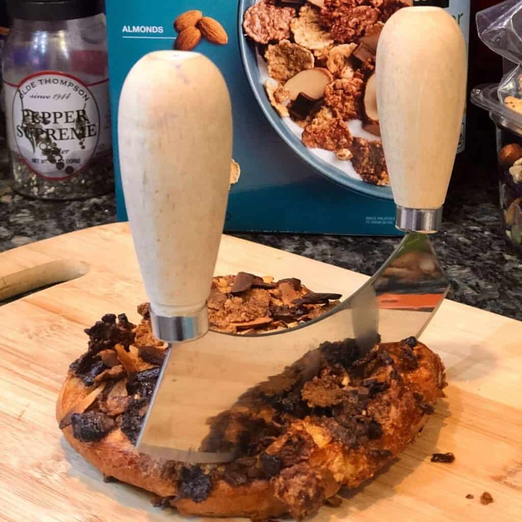 Cutting French toast sticks with a curved chopper on a wooden cutting board with a box of cereal in the background