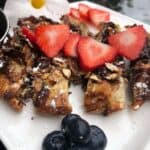 French toast crunch sticks with sliced strawberries on top on a white plate with blueberries and a white flower