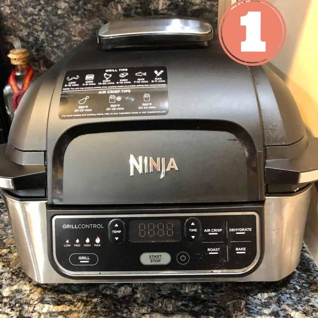 Ninja Foodie Air Fryer Griller sitting on a black granite counter top